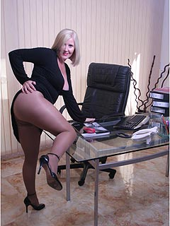 Mature lady boss is sharing pictures of herself exposed taken in the office: big boobs and legs in pantyhose are featured