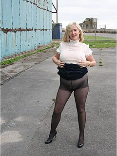 This mom is totally shameless: lifting up her skirt and showing off pussy in black pantyhose
