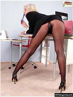 MILF is alone in the office: taking down her clothing and masturbating through pantyhose on top of the table