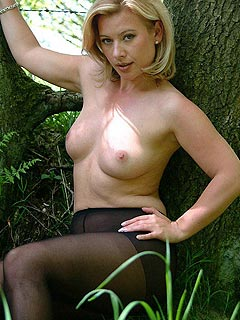 Blonde babe is walking out in the forest dressed up in black nylons only