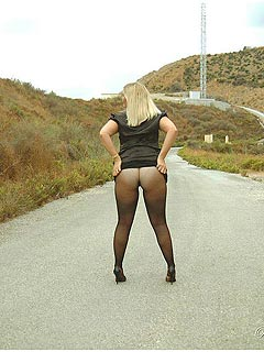 Horny mom is showing off her pantyhose legs and big boobs in the middle of the road