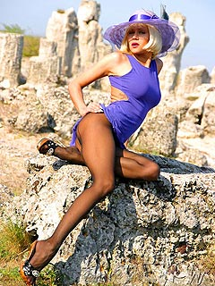 Hot babe is taking kinky poses on the rocks to let you enjoy her long legs in black pantyhose