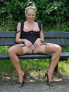 Exhibitionist blonde is walking in the park spreading her legs and flashing with her pussy