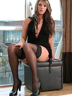 The view of an office girl posing at the window with her legs in black stockings and high heel shoes