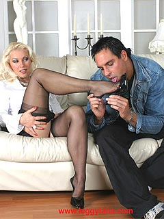 A couple is enjoying each other: he is worshiping sexy feet in black nylons and she is working out his cock with her toes