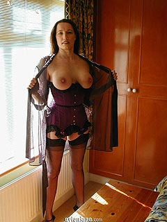 MILF mistress is in her bedroom: wearing a set of black lingerie with heels and black stockings