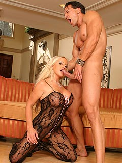 MILF with big fake tits is enjoying the taste of cum in her mouth and the feeling of fishnet body-suit rubbing her skin