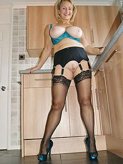 What is granny doing at the kitchen? Well she is acting like a total slut: showing off her bald cunt and legs in black nylons