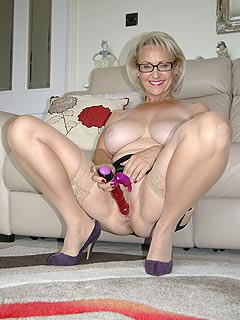 Granny is enjoying herself in lingerie and using sex toys on camera while smiling a lot