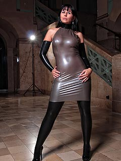 Girl is making herself look glamorous by combining rubber mini-dress and a apir of latex stockings