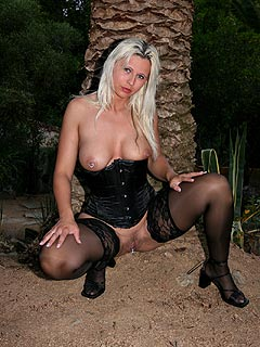 Slutty wife is ready for kinky photo session where she is to be wearing just tight corset with a pair of black nylons